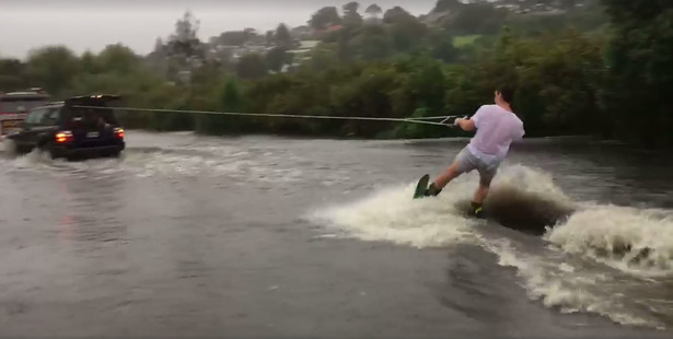 Loading A young man rides a wake board in Remuera flooding. Photo / Simon Hemmings