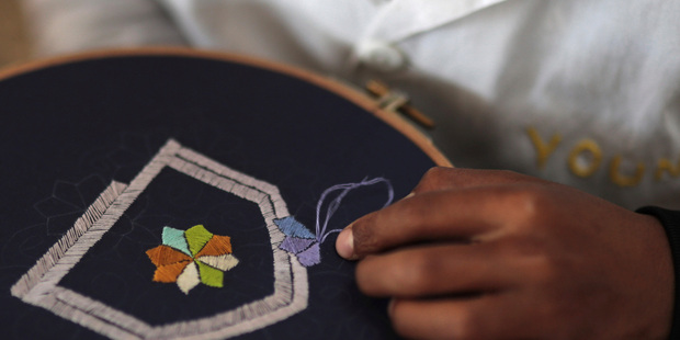 A boy learns embroidery in an informal school run by Moroccan fashion designer Fadila El Gadi, in Sale, near Rabat, Morocco. Photo / AP