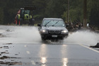 Vehicles make their way through debris and floodwater on State Highway 25 near Whangamata after heavy rain. Photo / Alan Gibson