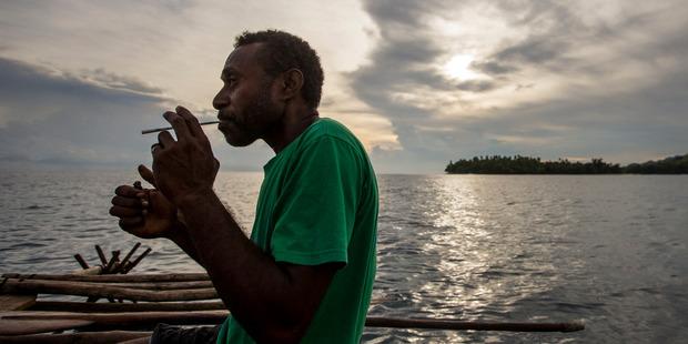 Nelson Manamuso enjoys a smoke on the water near the village of Kamasina. Photo / Mike Scott