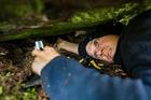Corey Mosen squeezing through the gap to get to a Kea nest. PHOTO/ DAVE BUCKTON