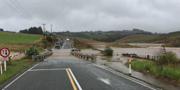Motorists driving through floodwaters on a one way bridge on Wiroa Rd, near Kerikeri, after thunderstorms across the region yesterday.  PHOTO/SUPPLIED