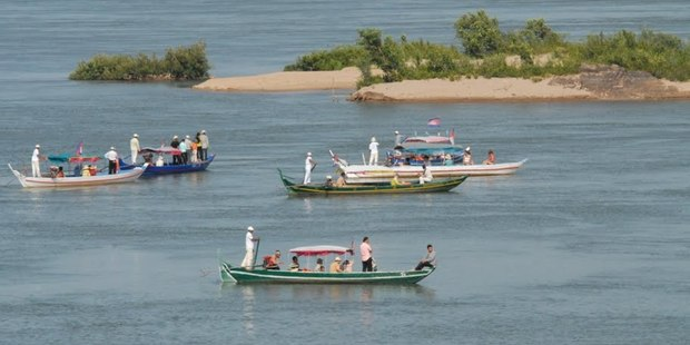 Tourist boats looking for dolphins in the Mekong River, Cambodia. Photo / GE Ryan