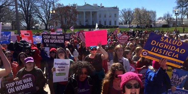 Scores of women participating in a 'Day Without a Woman' march make their way from Freedom Plaza to Lafayette Park past the White House. Photo / Washington Post