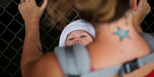 Nine-month-old Liv Dunbar looks up while hanging from a baby carrier. Photo / AP