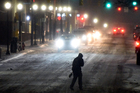 A pedestrian covers up from blowing snow while crossing the street in Pittsburgh. Photo / AP