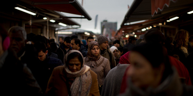 People walk along street stalls at a fruit market in The Hague, the Netherlands. Photo / AP