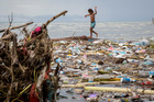 Children playing in the rubbish strewn shoreline at the Lord Howe informal settlement, Honiara. Photo / Mike Scott