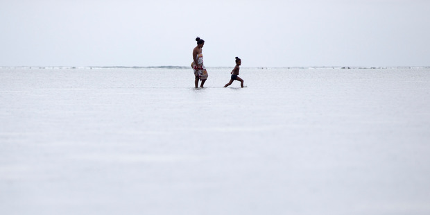 A mother and child search for shellfish near the village of Forau. Photo / Mike Scott
