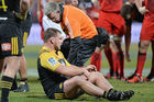 Reggie Goodes of the Hurricanes is assisted from the field after a concussion. Photo / Getty