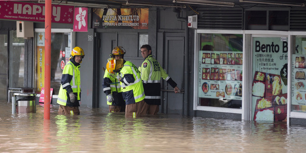 Fire Crews assist as a massive amount of rain caused a part of New Lynn town centre to flood. Photo / Dean Purcell