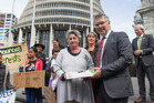 Bung the Bore founder Jen Branje presents a petition to Labour's David Parker outside the Beehive. The petition calls for a moratorium on freshwater exports. Photo / Mark Mitchell