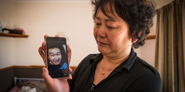 Loading Dongying Yuan holds the last photo of her son Enhe Zhou, who died in a motorbike crash.