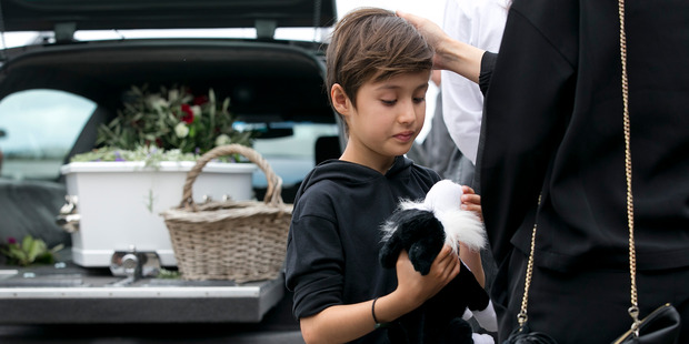 Jared Ball, 8, holds a stuffed Dog toy at the funeral of his grandfather and Footrot Flats creator Murray Ball which was held in Gisborne today. Photo / Alan Gibson