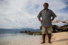 Francis Robeni stands on the beach. The small island behind him used to be part of the mainland. Photo / Mike Scott