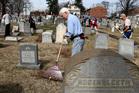 Volunteer John Walshrakes debris at Mount Carmel Cemetery in Philadelphia after the cemetery was vandalised. Photo / AP