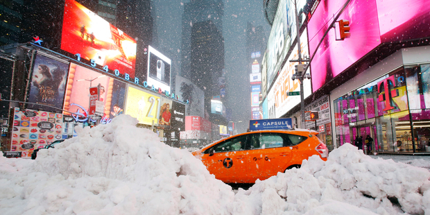 A taxi drives past piles of snow as a storm sweeps through Times Square, New York. Photo / AP