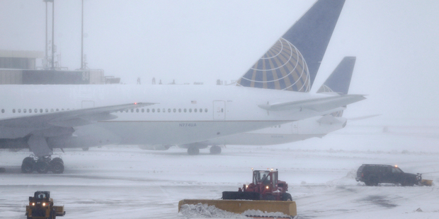 Snowplows work to keep the grounds clear at Newark Liberty International Airport. Photo / AP