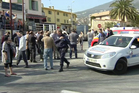 In this image from TV, police cordon off the area as people gather to view the nearby high school, following a shooting in Grasse, southern France. Photo / AP