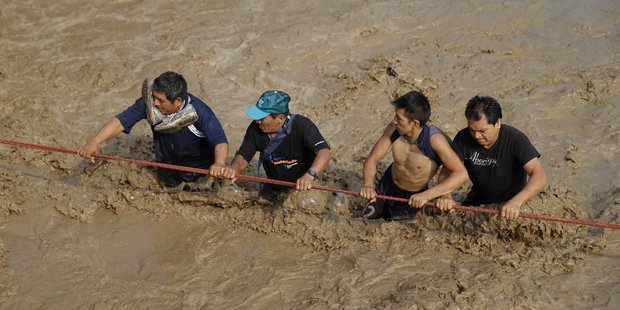 Men hold onto a rope as they wade through flood waters towards safety in Lima. Photo / AP