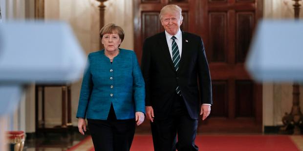 President Donald Trump and German Chancellor Angela Merkel walk down the Cross Hall of the White House. Photo / AP