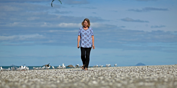 Thousands of dead shellfish washed ashore at Waihi Beach have shocked local residents, including Jeannette McCallum. Photo/George Novak