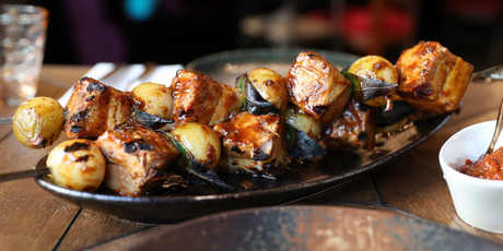 The shashlik - chargrilled spiced pork belly skewers with Russian ketchup. Photo / Getty Images