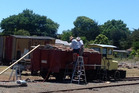Volunteers with the Ormondville Railway Preservation Group busy putting a new cover on vintage rolling stock.