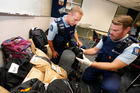 Area prevention manager for Whangarei and Kaipara Sergeant James Calvert, left, and Constable Denham Kelly sort through a mass of stolen gear found in a Whangarei. Photo/John Stone
