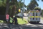 Ambulance staff help a child hit by a car while riding a bike on Maungatapu Rd. Photo/John Borren