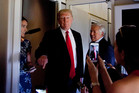 President Donald Trump talks to press corps inside Air Force One at the Palm Beach International Airport. Photo / AP