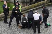 A policeman points a gun at a man on the floor as emergency services attend the scene outside the Palace of Westminster, London. Photo / AP