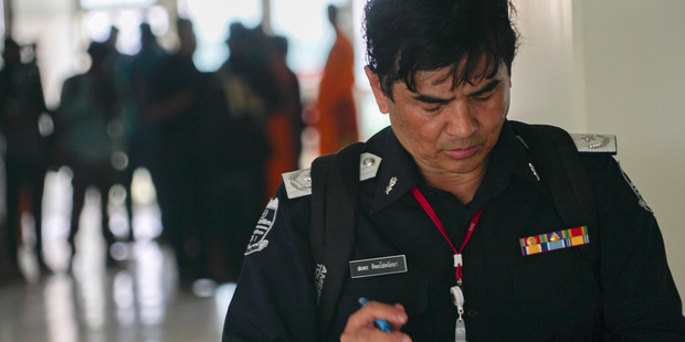 An officer checks his notes inside a medical centre on the Wat Dhammakaya temple compound in Pathum Thani province, Thailand. Photo / AP