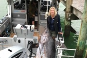 Nicky Sinden with the swordfish she caught off Northland. It was so big that part of the fish had to be left dragging in the water for the long trip back to shore. Photo / Supplied.
