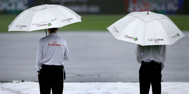 Umpires Rod Tucker and Bruce Oxenford inspect the Seddon Park pitch during a rain stoppage. Photo / Getty