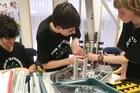 In an upstairs room at the House of Science in Tauranga, three high school students are frantically building a robot for the robotics world championship.