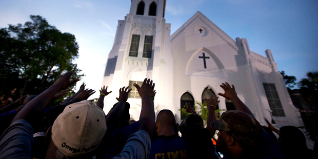 Loading A crowd of people in prayer outside the Emanuel AME Church, after a memorial for the nine people killed by Dylann Roof. Photo / AP