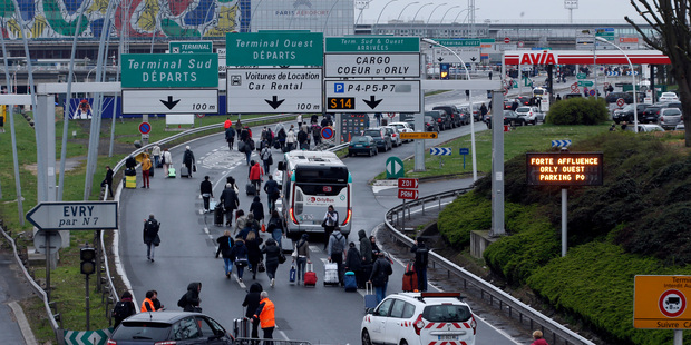 Travellers walk on the highway following the evacuation of Orly airport. Photo / AP