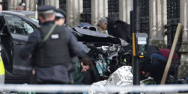 Loading Emergency personnel tend to an injured person close to the Palace of Westminster, London. Photo / AP