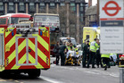Emergency services staff provide medical attention, close to the Houses of Parliament in London. Photo / AP