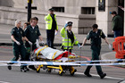 Emergency services staff provide medical attention close to the Houses of Parliament in London. Photo /