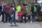 A girl lying on the ground is treated by passers-by on the Embankment near to the Houses of Parliament. Photo / AP