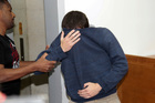 A 19-year-old dual US-Israeli citizen covers his face as he is brought to court on suspicion of making bomb threats to Jewish community centres in the US, New Zealand and Australia. Photo / AP