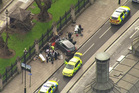 In this image taken from video police officers gather around a car adjacent to Houses of Parliament in London. Photo / AP