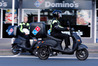Domino's franchise owner Jayesh Madhav rides one of the electric scooters used in Whangarei to deliver pizzas, while Te One Hamilton-Guest looks on. Photo / John Stone