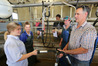 The students' big day out at Patoka, Millie O'Hagan (left), of Feilding, learns the finer arts of the dairy shed with farm owner BDO host Nick Dawson, in the milking shed. Photo/Duncan Brown