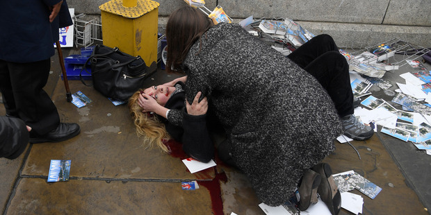 Loading Melissa Cochran is comforted as she lies injured after the attack at Westminster yesterday. Photo / Reuters