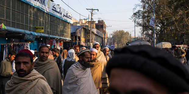 Men gather on a main street in Jalalabad, hoping to find a scarce job paying US$8 a day. Photo / Washington Post