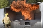 A firefighters shows what not to do in a kitchen fire as part of a New Zealand Fire Service demonstration at the TECT Trustpower Rescue Helicopter open day. Photo/George Novak
