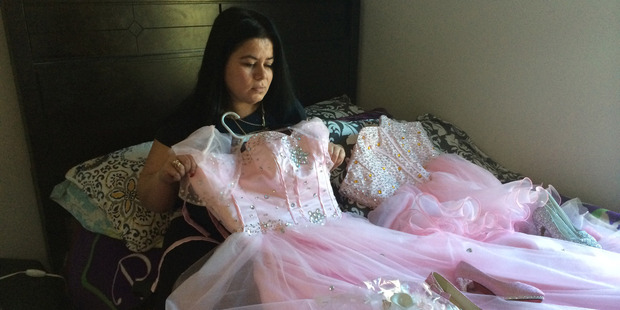 Maria Reyes holds a dress of her 15-year-old daughter Damaris whose body was discovered February 11. Photo / Dan Morse, Washington Post